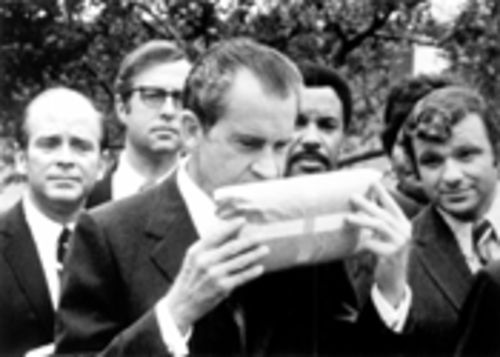 Richard Nixon sniffs a package of marijuana