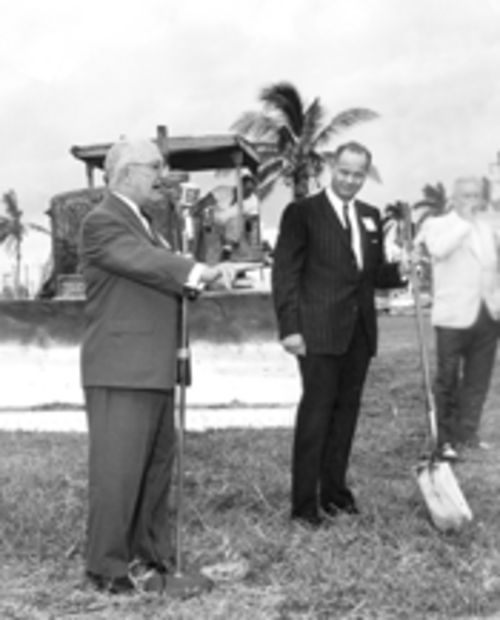 January 1965: At the Shops' groundbreaking ceremony, Stanley Whitman (leaning against shovel) waits impatiently for Bal Harbour Village founder Robert Graham to wave him into the future