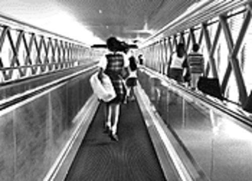 A merry-go-lucky schoolgirl hops down the moving walkway in the Dolphin garage, which has been shut down for months in a cost-cutting move by the county's Aviation Department