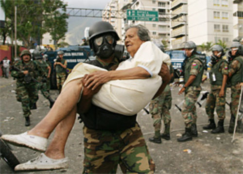 A guardsman carries a woman affected by tear gas in Caracas during the March 2004 Guarimba riots