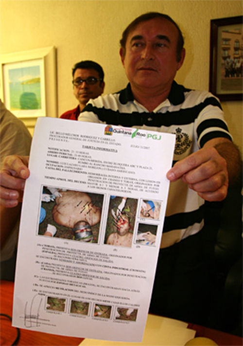 Mexican Prosecutor Bello Melchor Rodríguez holds up the autopsy report of Luis Lázaro Lara Morejón, a 30-year-old Cuban-American murdered for his role in a human smuggling ring.