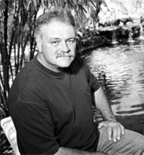 Paul Radice sits in front of his show pond, home of the  prized koi