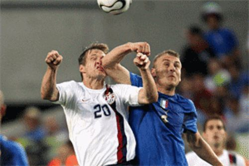 Daniele De Rossi smacks the USA's Brian McBride in fine Italian fashion
