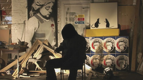 Banksy's face is shrouded in a dark hood.
