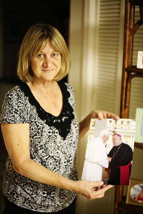 Wenski's sister, Mary Engle, shows off a photo of her brother meeting Pope Benedict XVI at the Vatican in June.