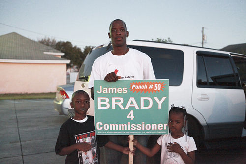 James Brady holding a sign moments before the polls close January 24.