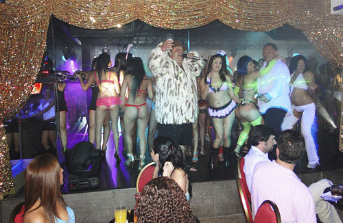 Surrounded by Colombian strippers, Galeota gives a toast during a party at the Doll House.