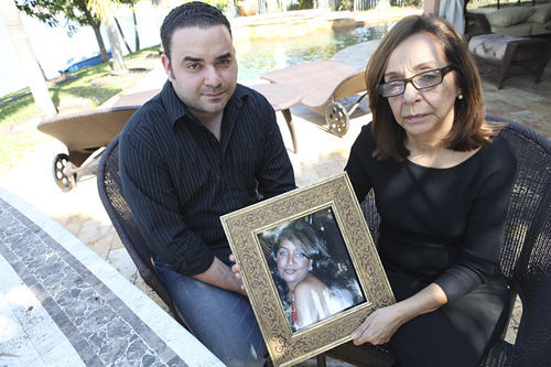 Hernandez's brother, Manuel Cedeño, and mother, Elsa Peña Nadal, hold a picture of her.