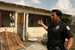 Ofcr. Pete Rojas indicates a recently burned-out crack house on Superior Street; sometimes fire is the only method of resolving such nuisances in the town