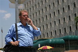 John Schmidt chats on his cell phone before entering the Miami-Dade courthouse, where he helps criminal drug offenders avoid jail time