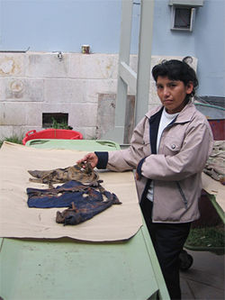 Teófila Ochoa, age 35, stands with clothes found that might have belonged to her brother, Gerardo, one of her five siblings gunned down by Peruvian army soldiers