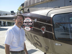 Michael Doyle, executive director of the Florida Keys Mosquito Control District, stands next to one of the four helicopters used to wage aerial assaults on mosquitoes.