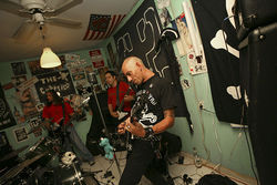 Gil Ortiz Pla (right), in full punk regalia and Mohawk, rehearses with G2 in their cramped Flagami studio.
