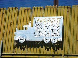 In this artwork, on the border fence in Nogales, Sonora, the skulls stuffed in the back of a truck illustrate violence immigrants experience at the hands of Border Patrol agents. Also, that many immigrants do not survive the journey.