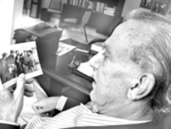 Eloy Gutierrez-Menoyo looks at a photo of Cuban  revolutionaries from the Fifties