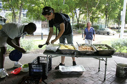 Haylee Becker prepares food for the weekly sharing in Stranahan Park.