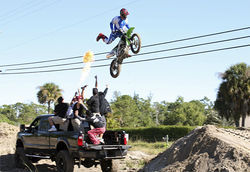 As part of a radio stunt, Rob jumps a dirtbike over a truck full of friends.