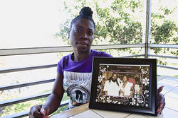 Claudine Magloire with a photo of her friend and lover, now deceased, Wildrick Guerrier.