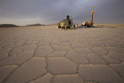 Workers test lithium levels at drill sites around Bolivia's salt flat.