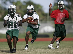 Running back Devonta Freeman (center) takes a handoff from quarterback Rakeem Cato.