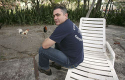 Former chicken cop Lesther Jorge perches in an Overtown yard invaded by cluckers in his absence.