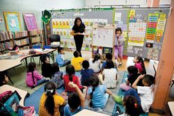 First-grade teacher Elizabeth Chavez at the whiteboard with Leslie Alvarez in the all-English class.