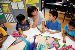 Reverend Callaghan teaches sentence structure to first-graders Danielle Trinidad (left) and Angel Otamendi.