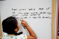 First-grader Daniela Saquich, already fluent in English, writes a rhyme she liked in her book.