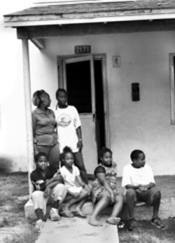 Octavia and five of her six children on the front porch of their Scott Homes apartment. Standing from left, Octavia and daughter Shawntai Marius, eighteen. Sitting from left, Alexander Hardemon, twelve; Phillecia Hardemon, ten; Ashley Hardemon, nine; and Phillip Hardemon, fifteen