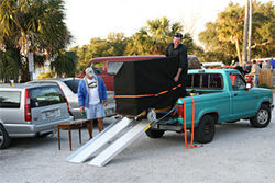 Kris Hull unloads his piano with the help of a winch installed in his truck bed.