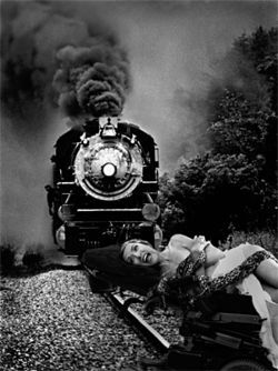 With the magic of Photoshop, Ann Thomas is tied to train  tracks like a helpless heroine from movies past