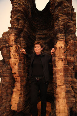 Ursula von Rydingsvard stands next to one of her colossal sculptures.