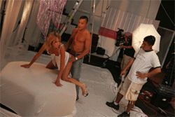 Actors and the set crew block a sex scene